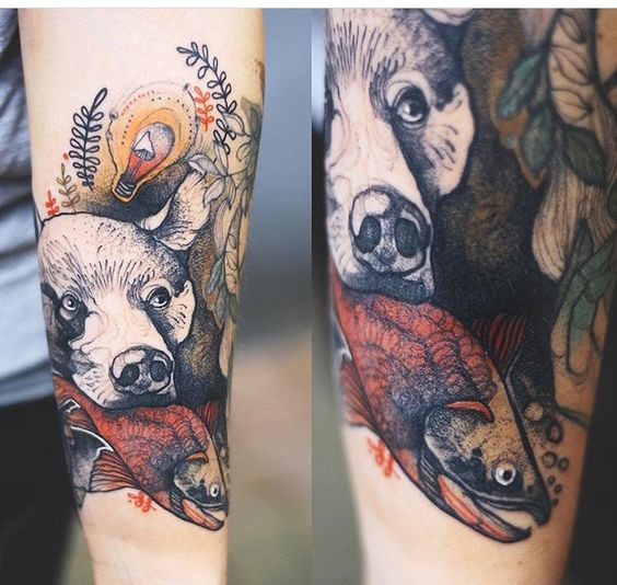 Strange looking colored by Joanna Swirska forearm tattoo of bear head with fish