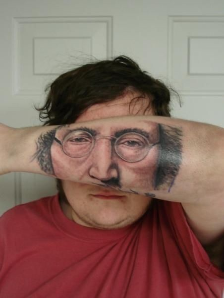Strange looking colored Lennon face tattoo on arm