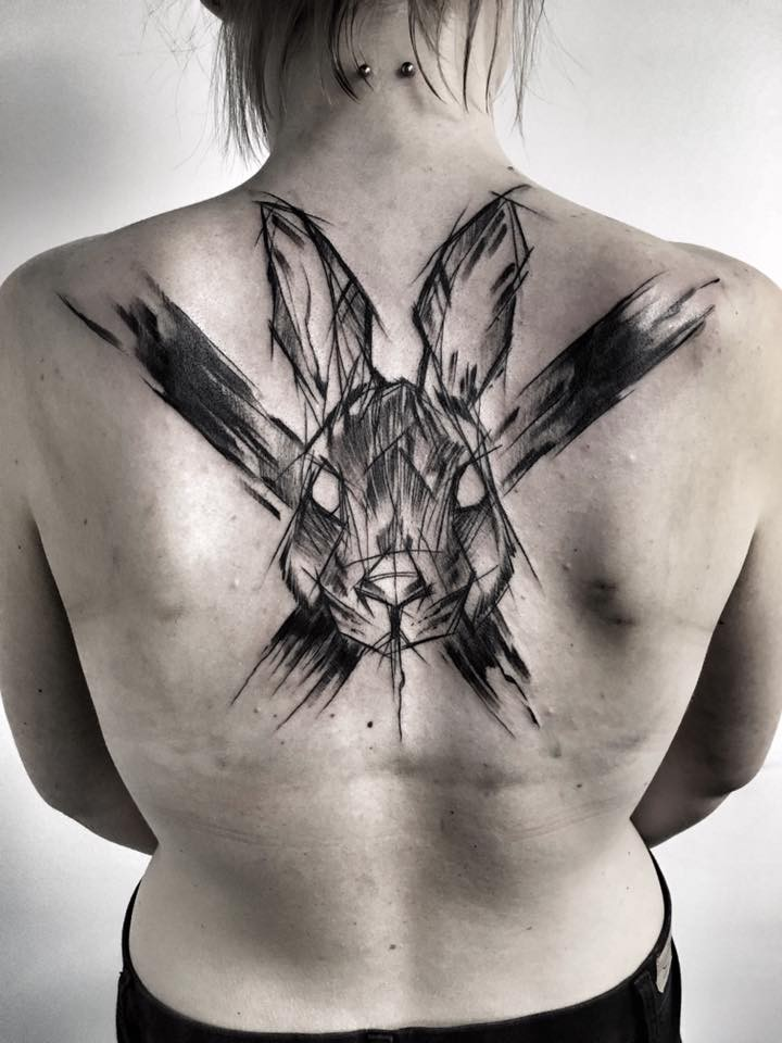 Strange looking sketch style painted by Inez Janiak upper back tattoo of rabbit with big cross