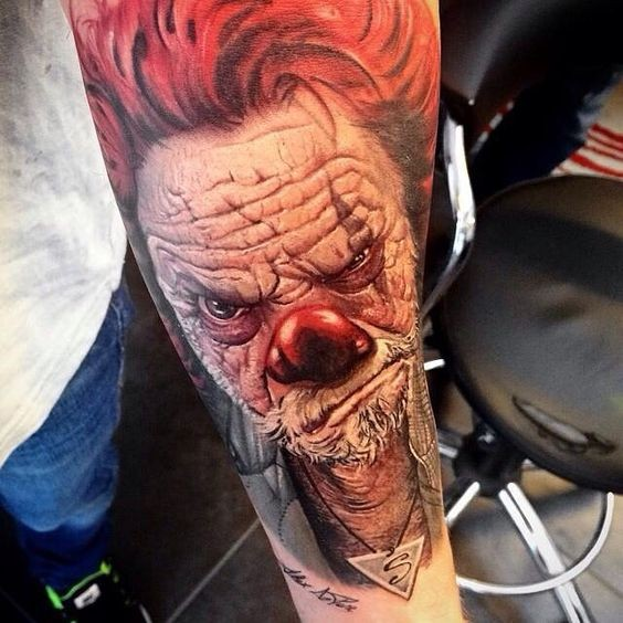 Stunning 3D detailed and colored forearm tattoo of old corrupted clown