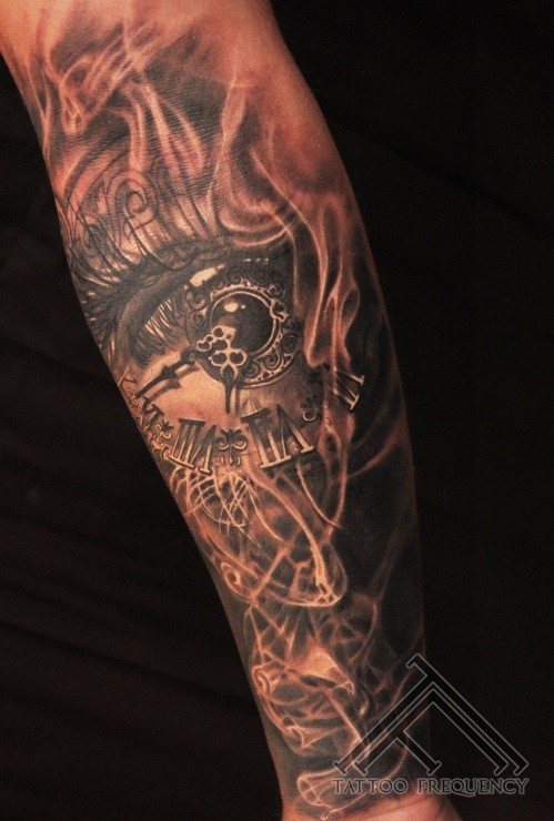 Stunning black ink forearm tattoo of human eye with clock