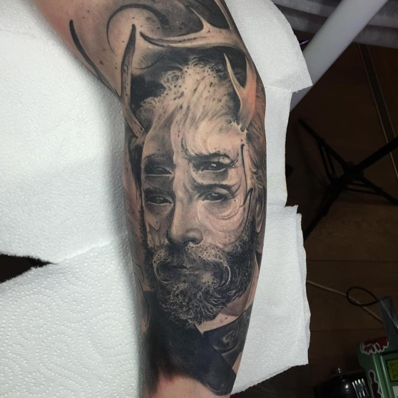 Stunning black ink sleeve tattoo of demonic man face