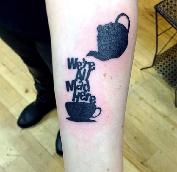 Stunning black ink tea cup with lettering tattoo on arm