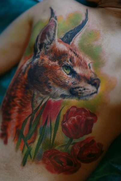 Stunning breathtaking looking colored realism style back tattoo of wild cat with flowers