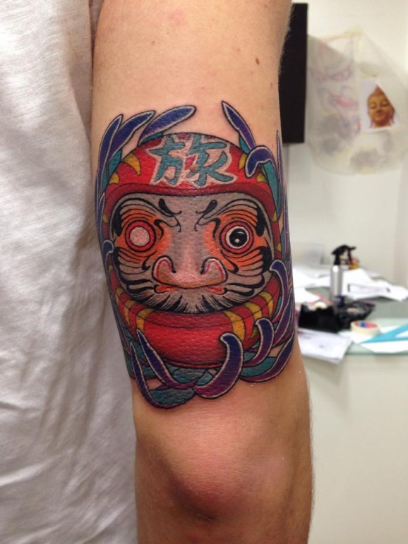 Stunning colored arm tattoo of daruma doll with lettering and flowers
