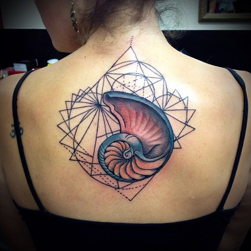 Stunning colored back tattoo of big shell with geometrical figure