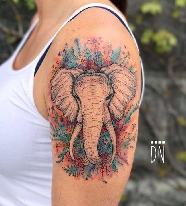 Stupenda colorazione del tatuaggio di Dino Nemec sul braccio superiore della testa di elefante con fiori