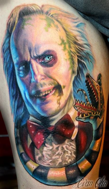Stunning colored horror style large thigh tattoo of creepy clown with alien like snake