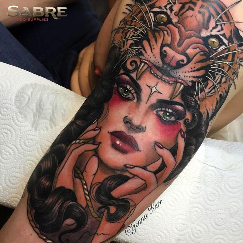 Splendido tatuaggio colorato del braccio superiore di una donna antica con elmo in pelle di tigre di Jenna Kerr