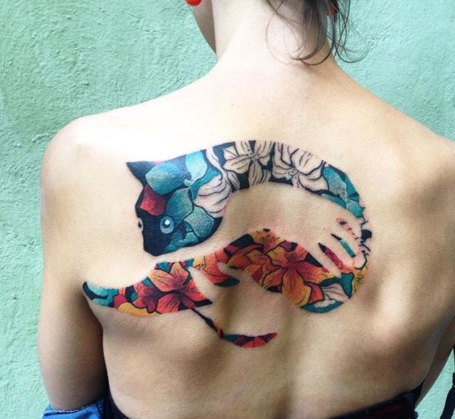 Stunning colored upper back tattoo of human hand holding cat stylized with leaves