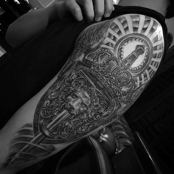 Stunning looking black and white shoulder tattoo oof big sword with shield stylized with lion