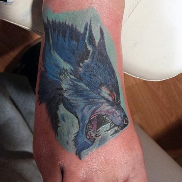 Stunning multicolored foot tattoo of werewolf head
