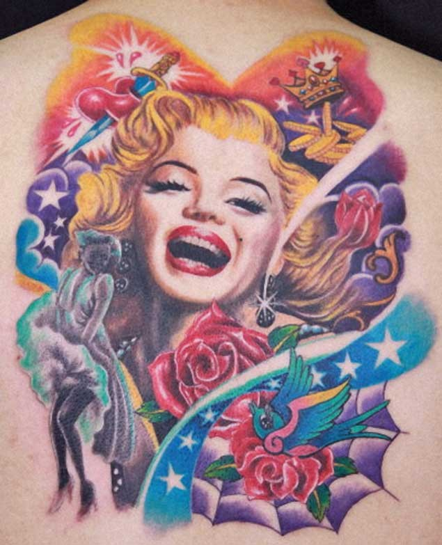 Stunning multicolored smiling Merlin Monroe portrait tattoo on back combined with various colored symbols
