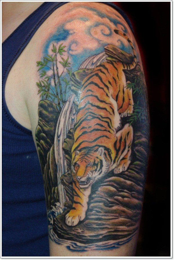 Stunning painted and colored realistic tiger near waterfall tattoo on shoulder