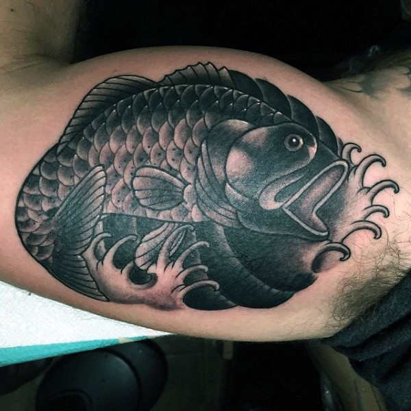 Stunning painted detailed black ink fish tattoo on biceps