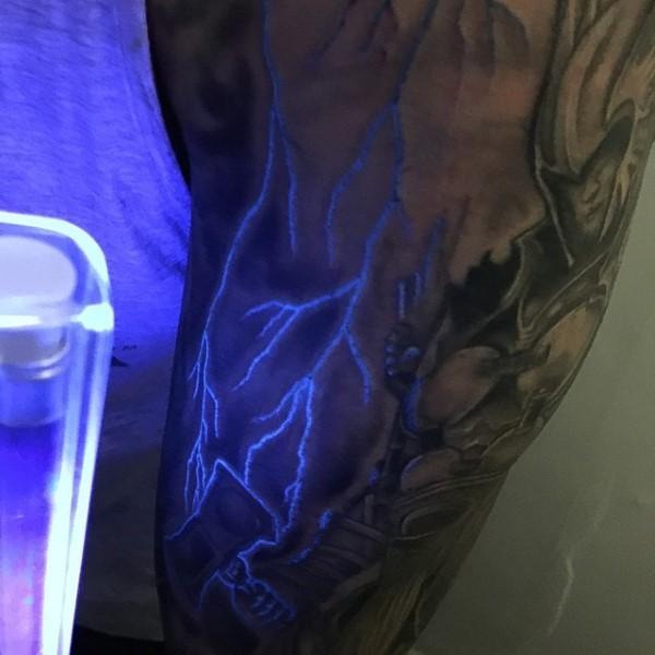Stunning painted glowing lightning tattoo on arm