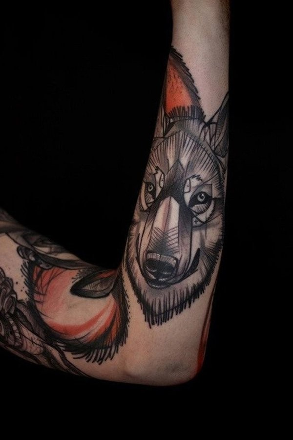 Stylized colored wolf&quots head forearm tattoo in original technique