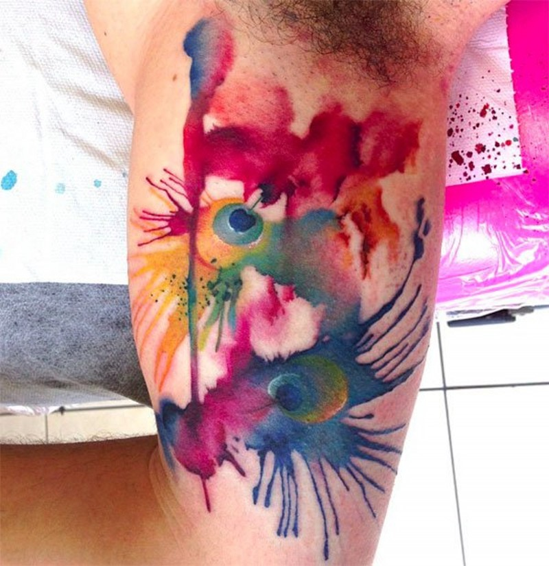 Stylized multicolored watercolor peacock feather tattoo on biceps with paint drips