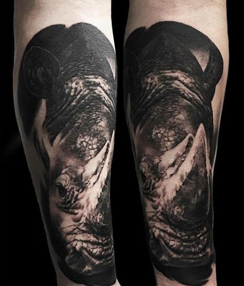 Super detailed 3D lifelike rhinoceros forearm tattoo in dark colors