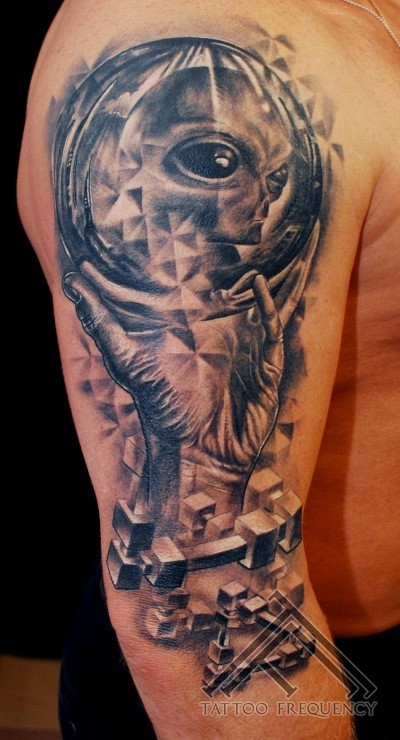 Superior black ink human hand with orb tattoo on shoulder stylized with alien face
