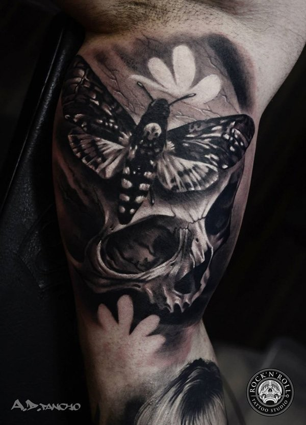 Superior realism stye black and white biceps tattoo of human skull and night butterfly