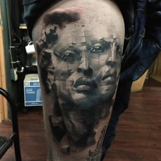 Surrealism style black and white thigh tattoo of alien face