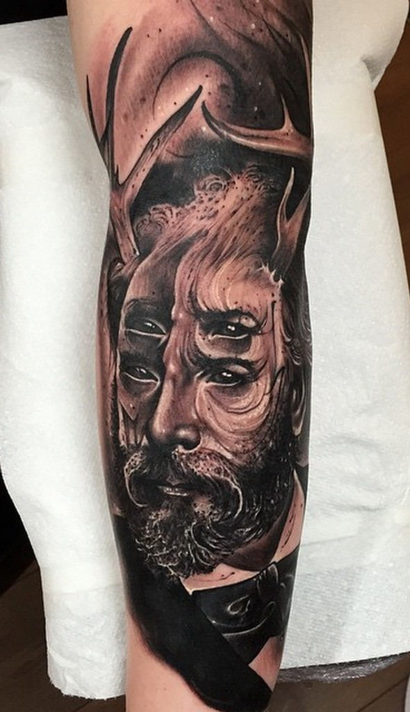 Surrealism style black ink arm tattoo of man with deer horn and four ...