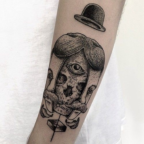 Surrealism style black ink arm tattoo of creepy human face