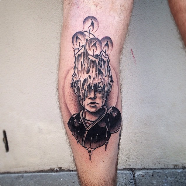 Surrealism style black ink leg tattoo of human face covered with burning candles