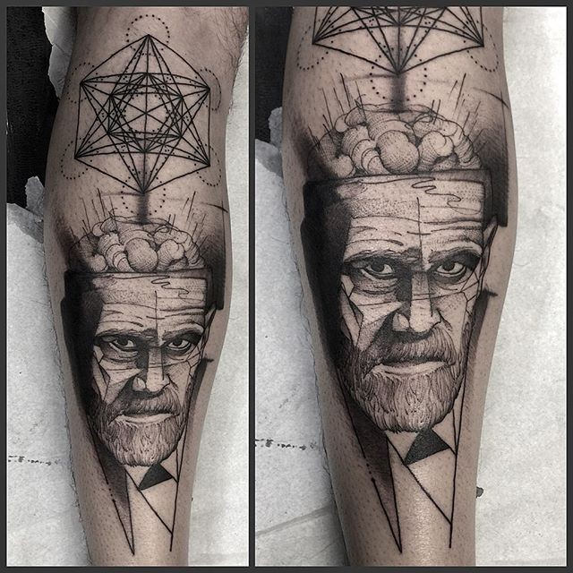 Surrealism style black ink leg tattoo of man face with various symbols