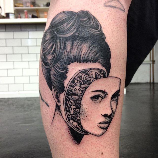 Surrealism style black ink leg tattoo of biomechanical woman face