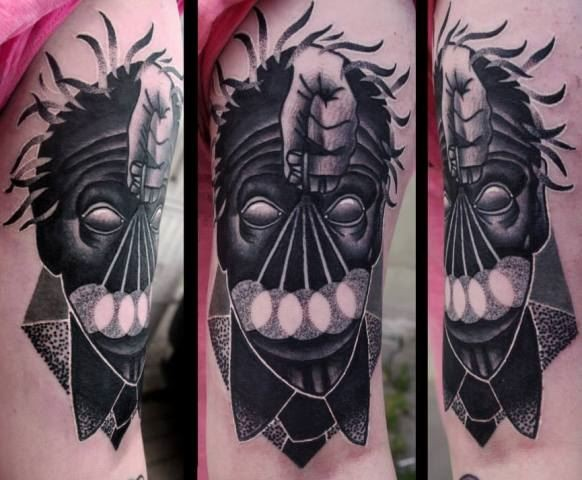 Surrealism style colored biceps tattoo of mystical face