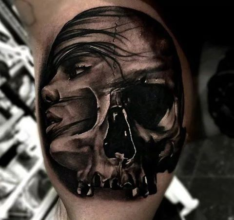 Surrealism style colored biceps tattoo of woman face with skull