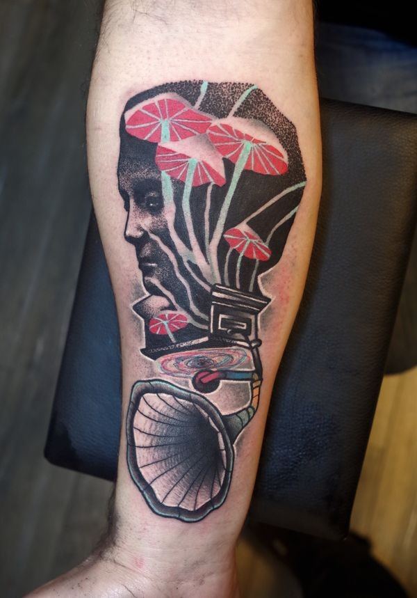 Surrealism style colored forearm tattoo of gramophone and man portrait