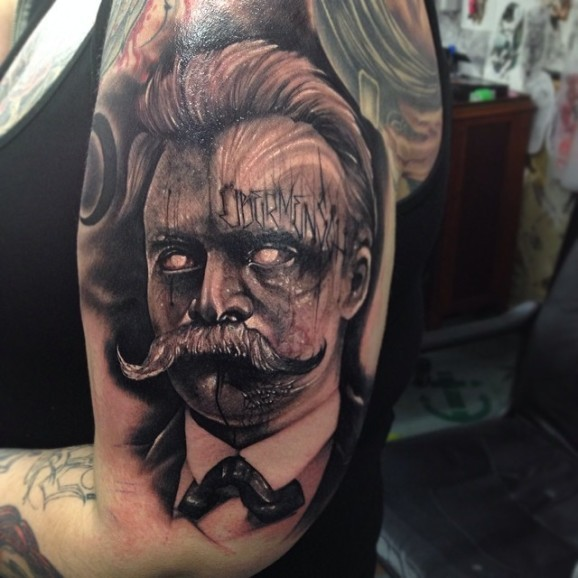 Surrealism style colored shoulder tattoo of man with lettering