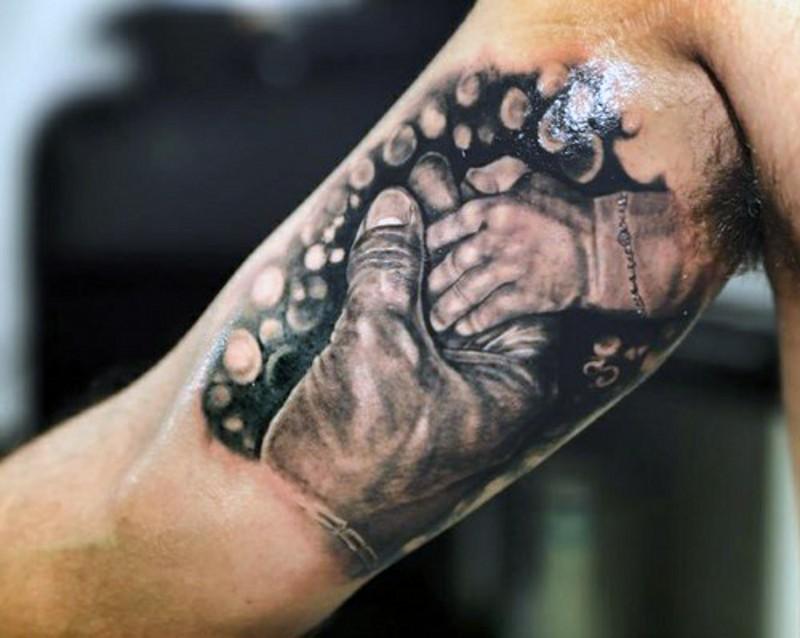 Tatuaje en el brazo, manos tiernos de padre y hijo