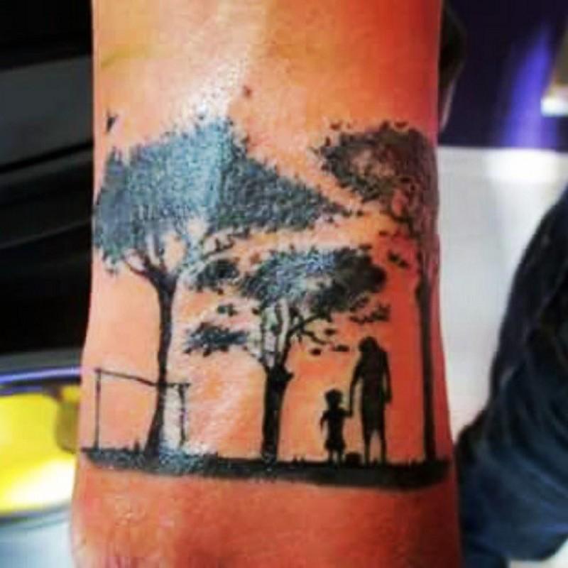 Tatuaje en el brazo, padre con hijo tiernos entre árboles