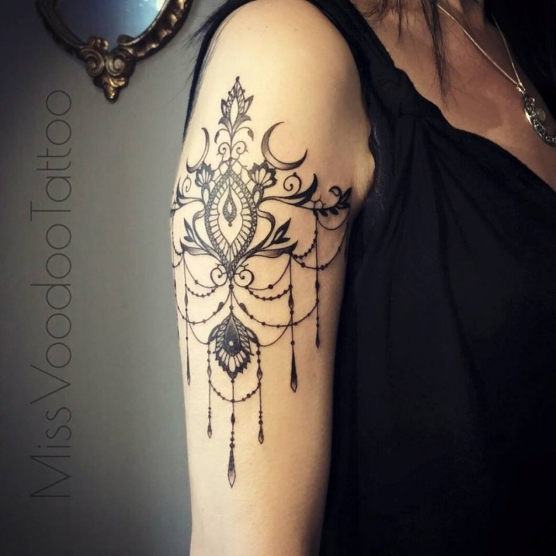 Sweet looking black ink painted by Caro Voodoo upper arm tattoo of floral ornaments with flowers