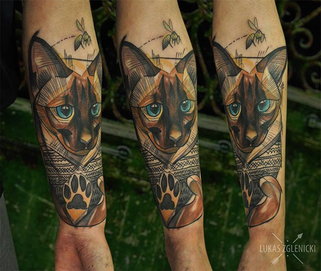 Sweet looking colored cat in sweater tattoo on forearm