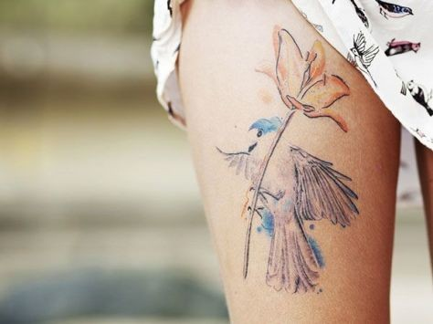 Sweet painted watercolor like big bird with flower tattoo on thigh