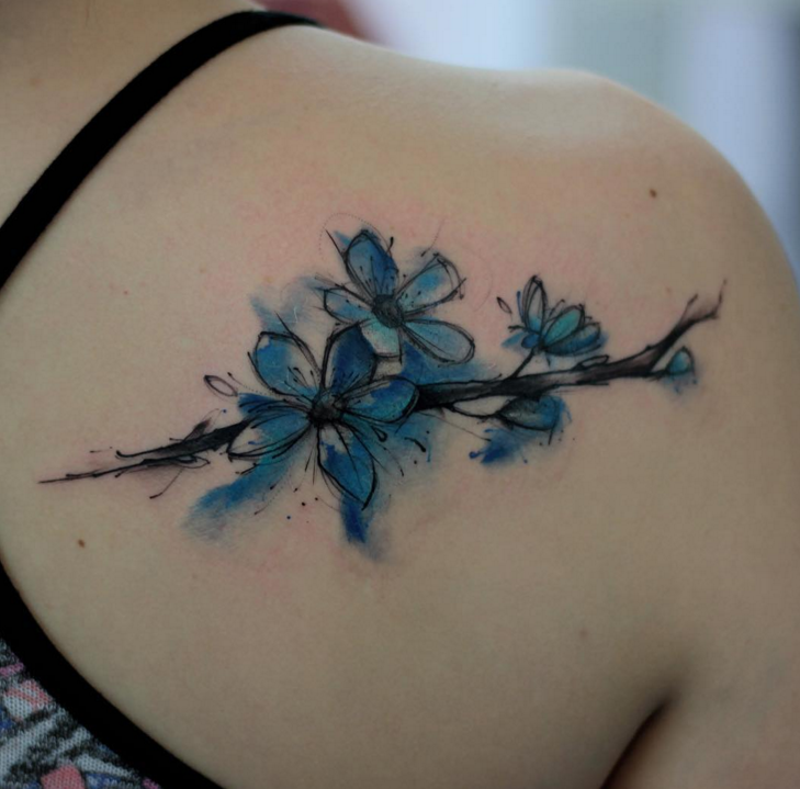 Sweet watercolor style back tattoo of tree branch with flowers