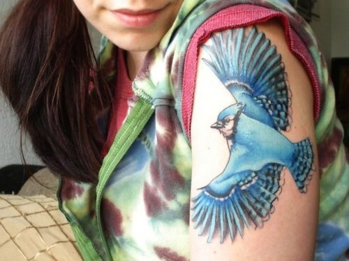 Swooping blue bird tattoo on shoulder
