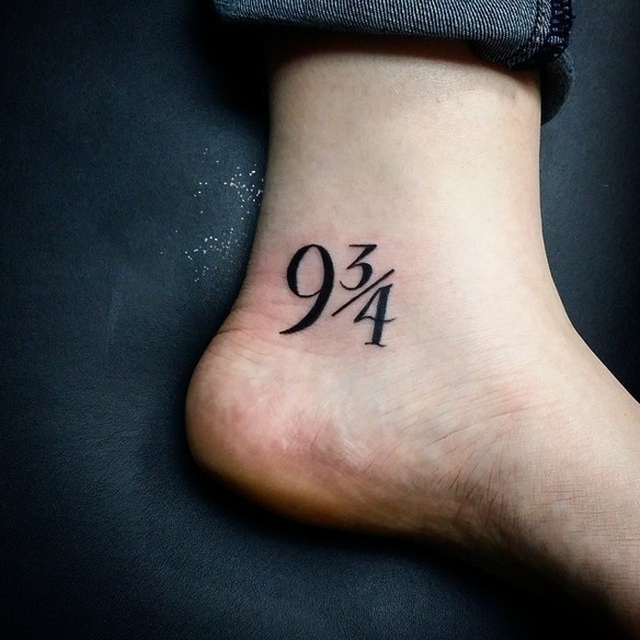 Symbolical numbers 9 3/4 tattoo on ankle in dark black ink