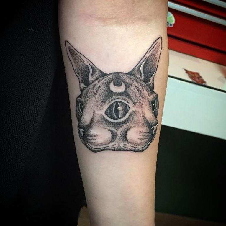 Symmetrical dot style forearm tattoo of mysterious cat with moon symbol