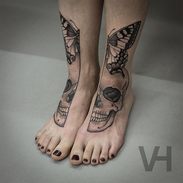 Symmetrical painted by Valentin Hirsch tattoo on legs of human skull and butterfly
