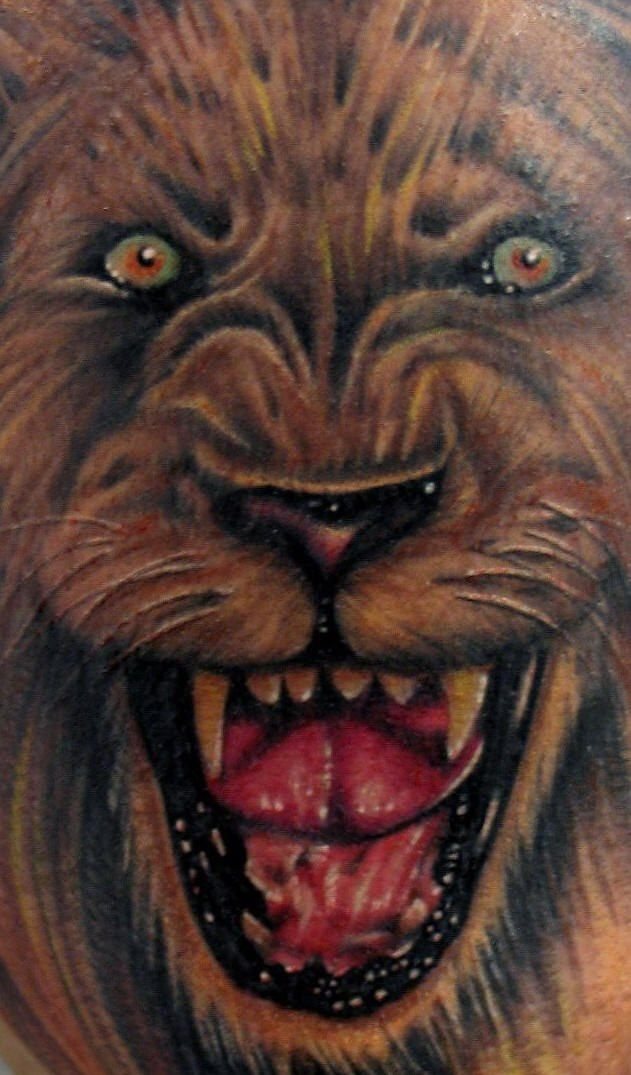 Realistic growling lion coloured tattoo