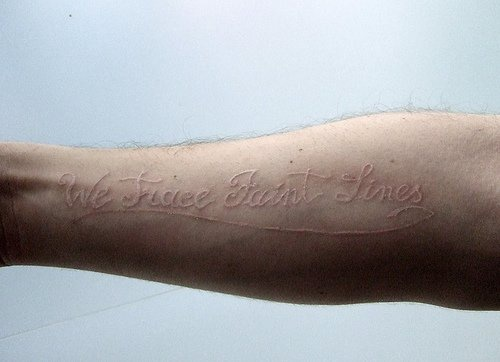 All white tattoo with inscription on hand