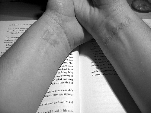 White ink tattoo with inscription on wrists