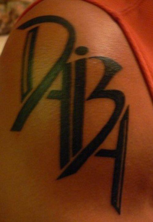 Disegno calligrafico tatuato sul deltoide