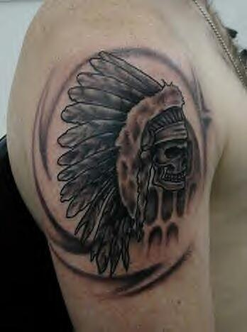Skull in feathers crown on shoulder